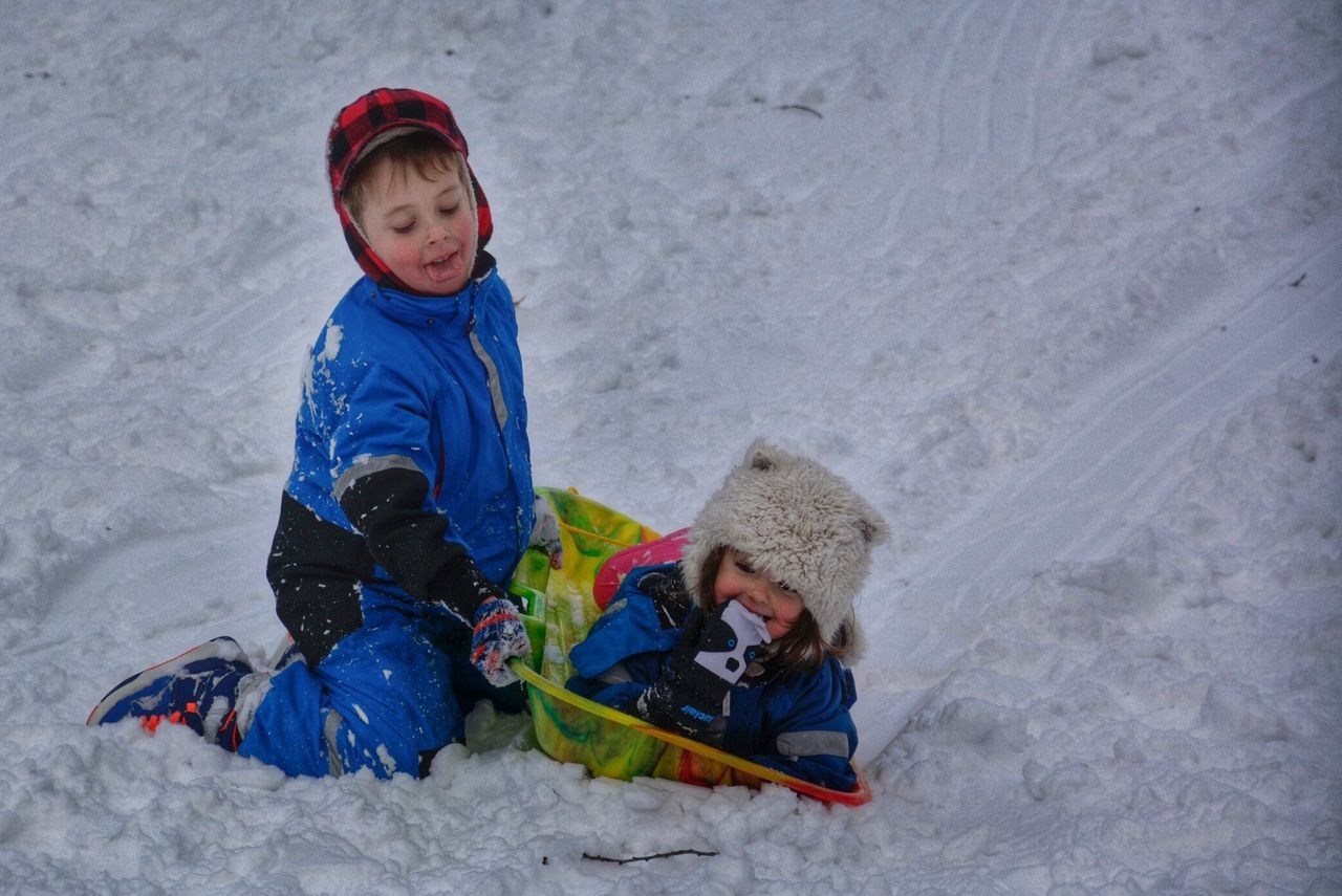 winter, snow, cold temperature, childhood, two people, warm clothing, lifestyles, high angle view, boys, real people, knit hat, togetherness, full length, outdoors, smiling, leisure activity, day, happiness, child, tobogganing, people, adult