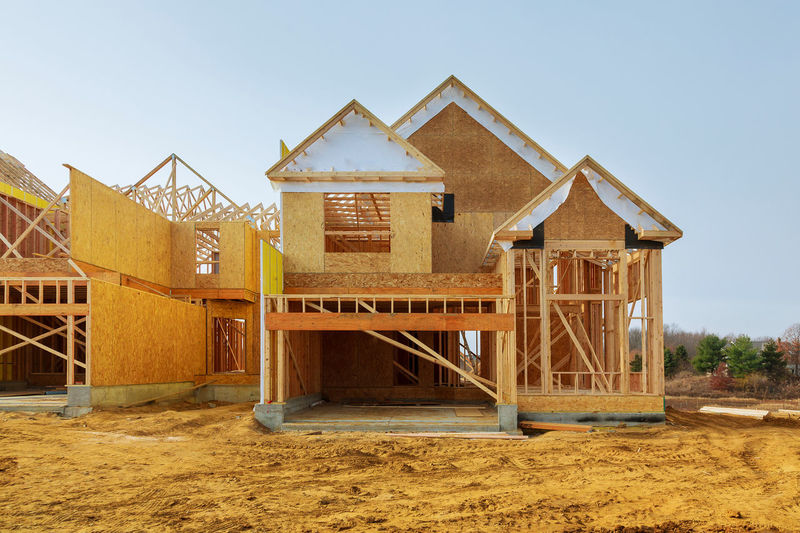 New construction of a house Framed New Construction of a House Building a new house from the ground up Construction Construction Equipment Framing Home Industrial Renovation Roof Under Unfinished Work... Architecture Beams Build Building Built Structure Dwelling Frame Framework House House Construction Housing Lumber Plywood Reconstruction Residence Residential Building