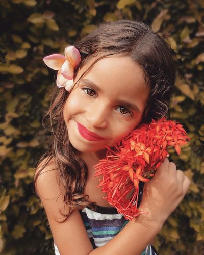 Close-up portrait of smiling girl holding flowers