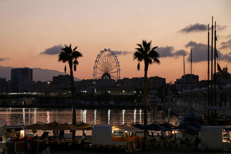 View of ferris wheel in city at sunset