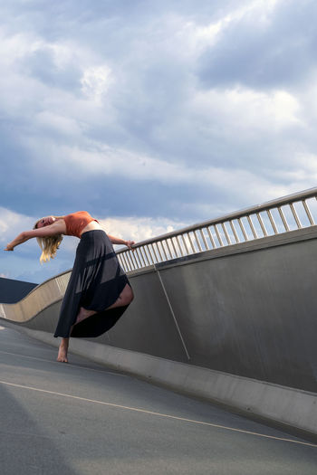 Side view of person skateboarding on bridge against sky