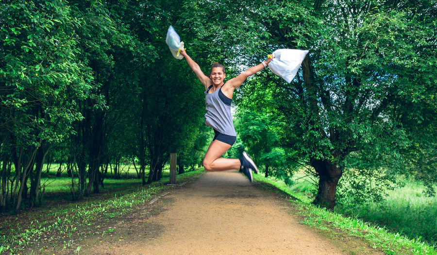 Portrait Of Cheerful Woman Holding Garbage In Plastic Bags While Jumping At Park
