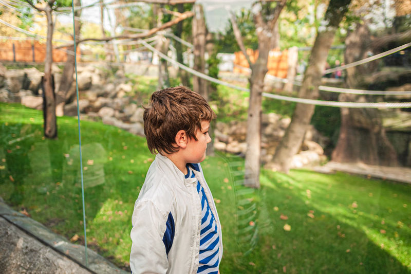 Boy looking away while standing at park