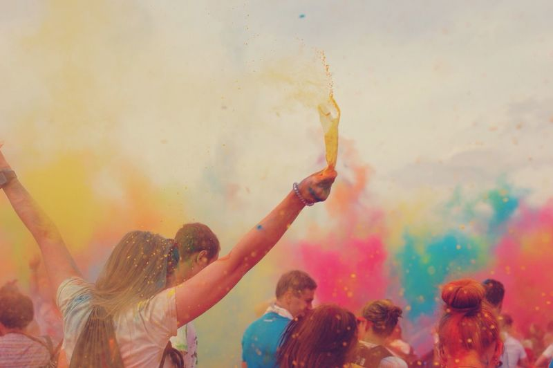 People throwing colored holi powder