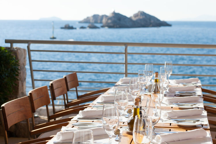 Chairs and tables at dining table by sea against sky