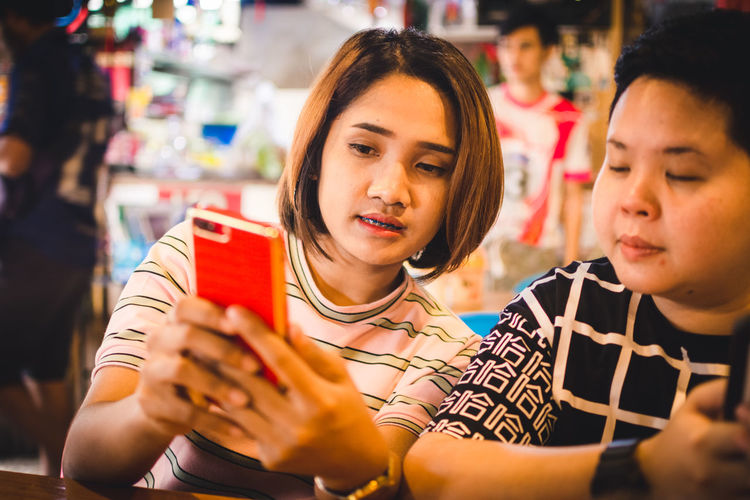Close-up of friends using mobile phone in shop