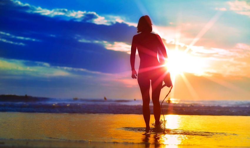 Rear view of woman at beach during sunset