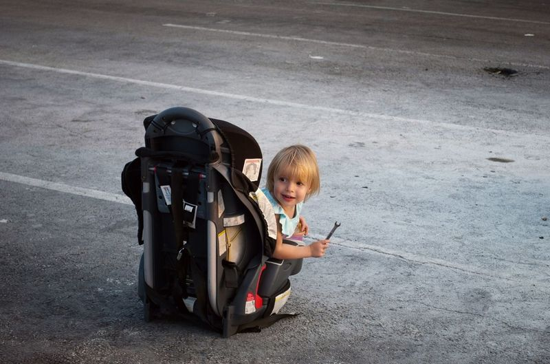 Girl Holding Wrench While Sitting On Seat At Parking Lot