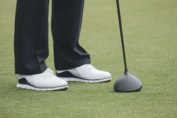 Low section of man standing on golf course