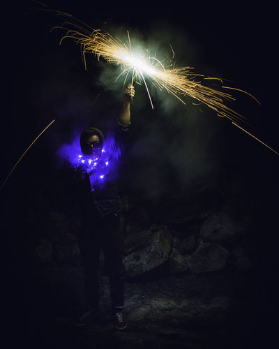 Sparky Arts Culture And Entertainment Blurred Motion Burning Celebration Dark Event Firework Firework - Man Made Object Firework Display Full Length Glowing Holding Illuminated Light Long Exposure Men Motion Nature Night One Person Real People Smoke - Physical Structure Sparkler Sparks Standing