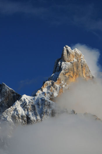 Scenic view of clouds over mountain against blue sky