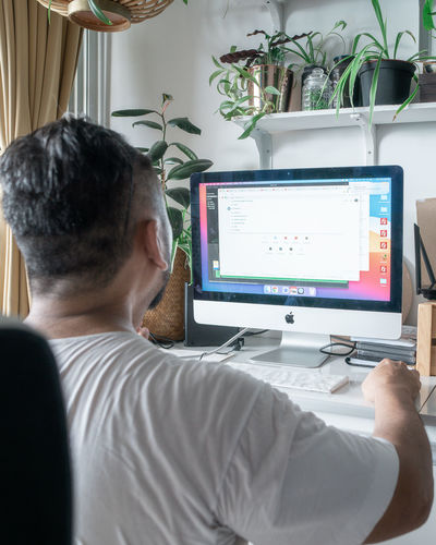 Rear view of man working on laptop