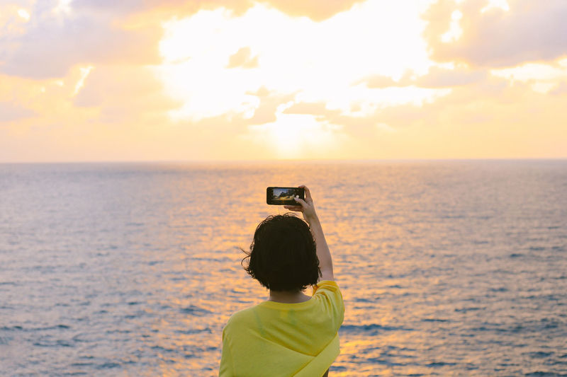 Rear view of girl photographing sea against sky during sunset