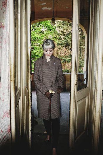 Portrait of woman walking through door