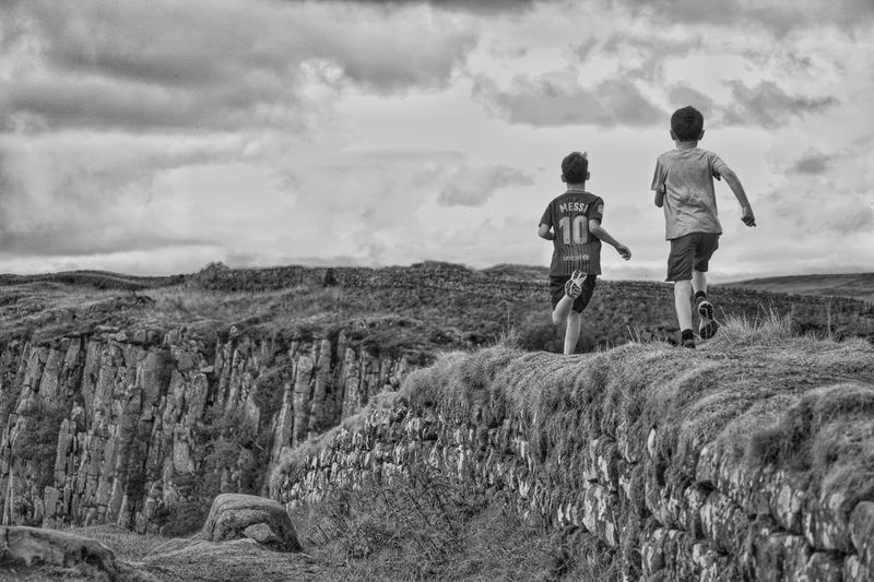 Rear view of children on land against sky