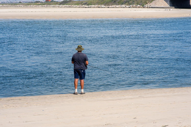Fishing Water Rear View Sea Real People Beach Men Land One Person Standing Day Lifestyles Nature Full Length Beauty In Nature Leisure Activity Outdoors Casual Clothing Sand Fishing