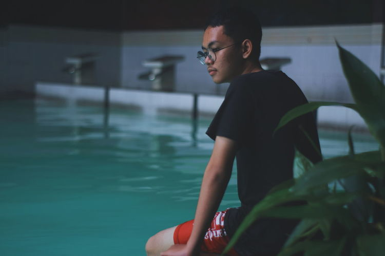 Young man sitting at poolside