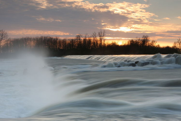 Scenic View Of Waterfall Against Sky At Sunset