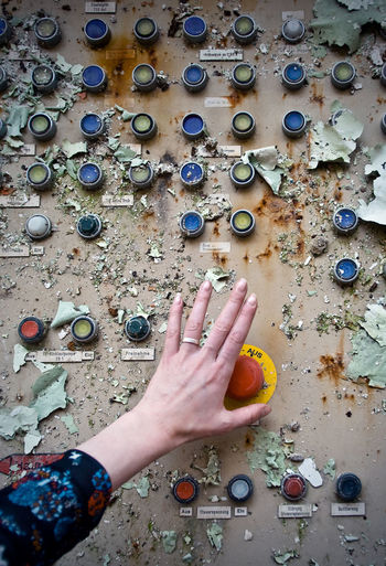 Close-up of woman pressing button of weathered machine