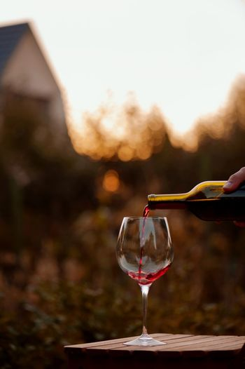 testing a glass of red wine at sunset Glass Wineglass Wine Refreshment Drink Alcohol Food And Drink Focus On Foreground Human Hand Red Wine Nature Day Holding Real People Outdoors One Person Hand Lifestyles Human Body Part Sky