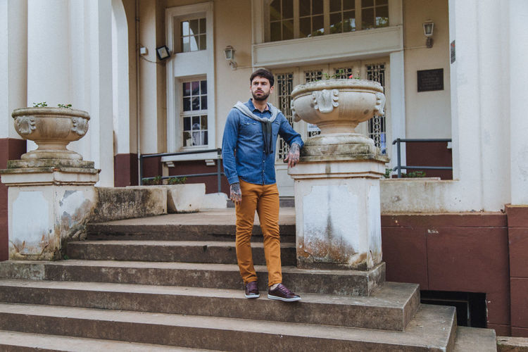 Full Length Of Young Man Standing On Staircase Against Building