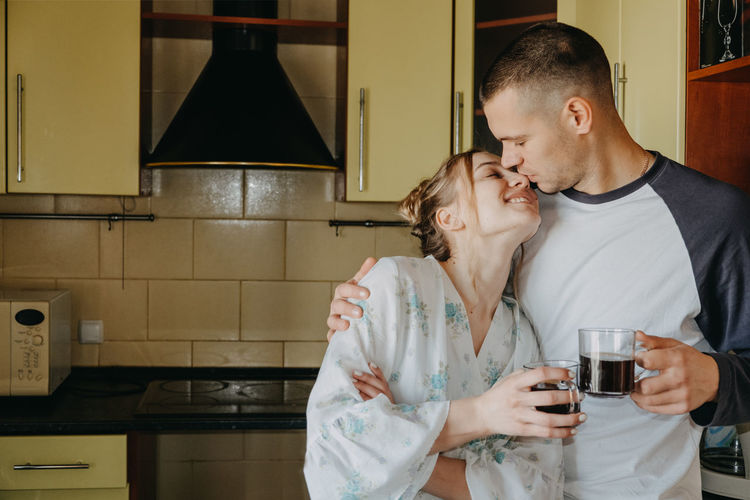 Couple holding coffee cup embracing in kitchen