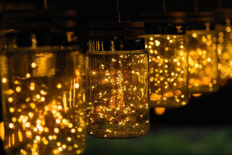Close-Up Of Illuminated Light Bulb In Jars