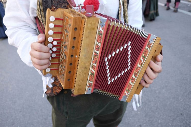 Midsection of man playing accordion while standing on road in city