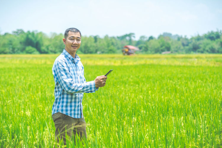 Portrait of man standing on field while using digital tablet