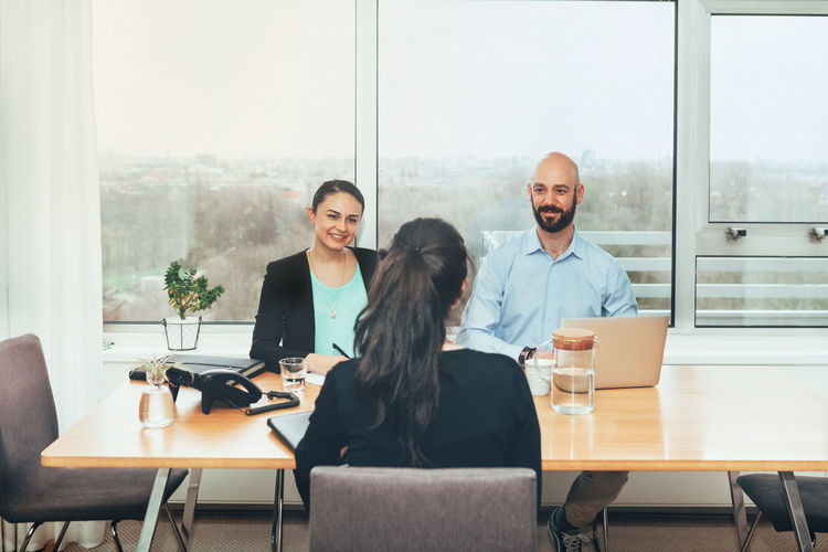 Business people taking interview of woman in office