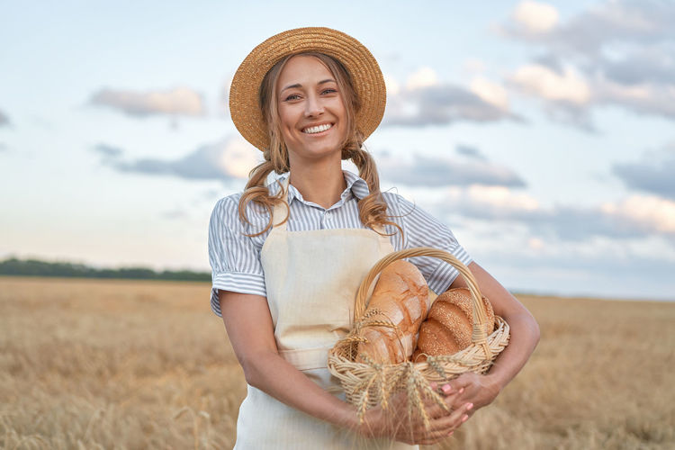 Portrait of smiling young woman standing in field