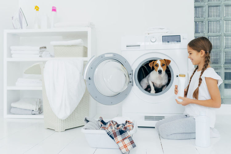 Girl looking at puppy sitting in washing machine