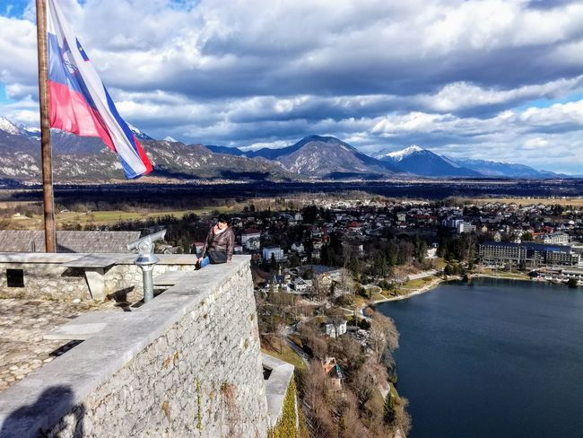 Bled castle view Patriotism Flag Mountain Sky Cloud - Sky Outdoors No People Day Water Mountain Range Architecture City Lake View Slovenia Travel Destinations Bled History Beauty In Nature Nature Reflection Built Structure Historical Building Bled Castle Architecture
