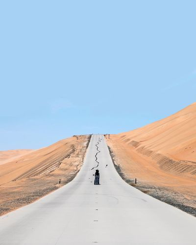 Person standing on country road in desert against clear blue sky