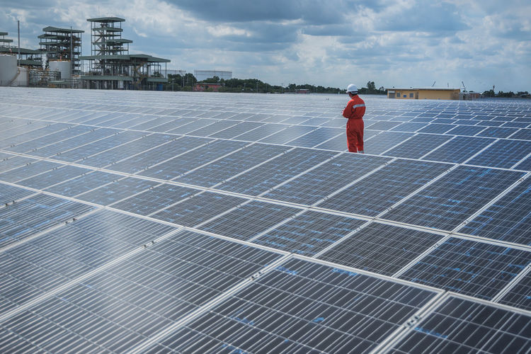 Manual worker working amidst solar panels against sky