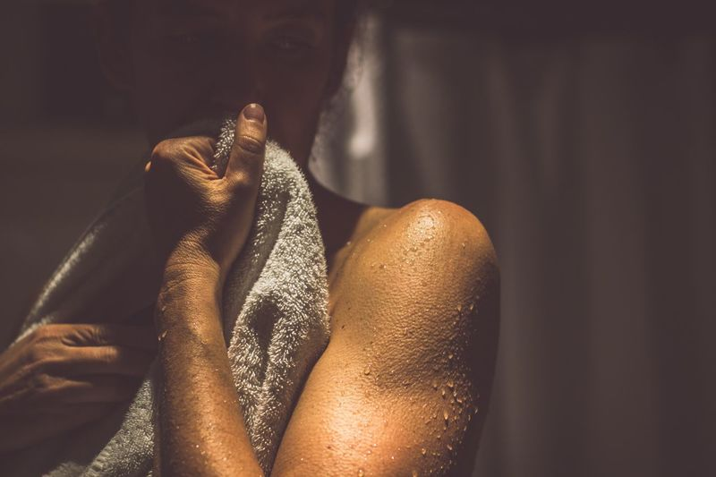 Thoughtful shirtless man holding towel in bathroom