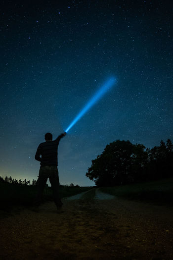 Torchman Astronomy Beauty In Nature Field Flashlight Full Length Holding Land Men Nature Night One Person Outdoors Real People Scenics - Nature Silhouette Sky Space Standing Star - Space