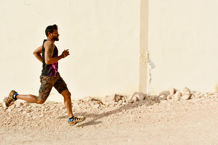 Side View Of Young Man Running By Building