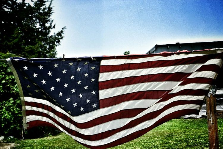 Low angle view of american flag against blue sky