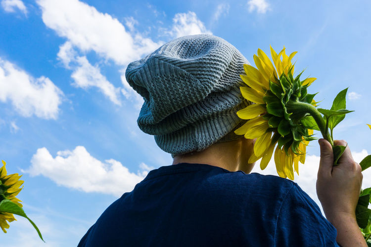 Low angle view of person in beanie holding sunflower against sky