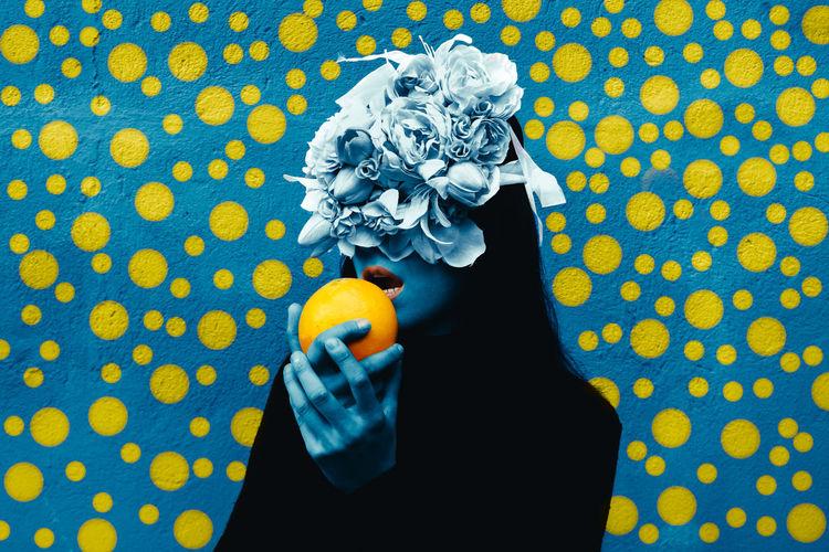Woman wearing flowers on hair holding orange fruit against wall