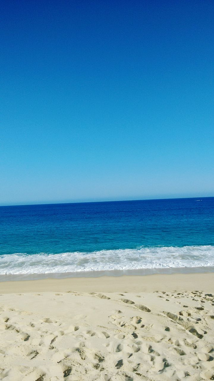 beach, sea, sand, horizon over water, blue, copy space, shore, clear sky, nature, scenics, water, beauty in nature, wave, tranquil scene, outdoors, tranquility, day, no people, vacations, sunlight, sky