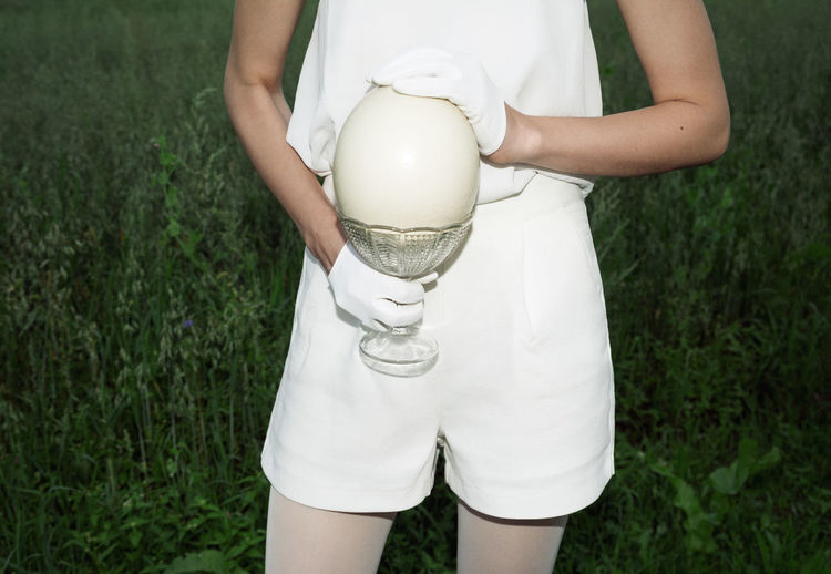 Midsection of young woman holding easter egg while standing on grassy field
