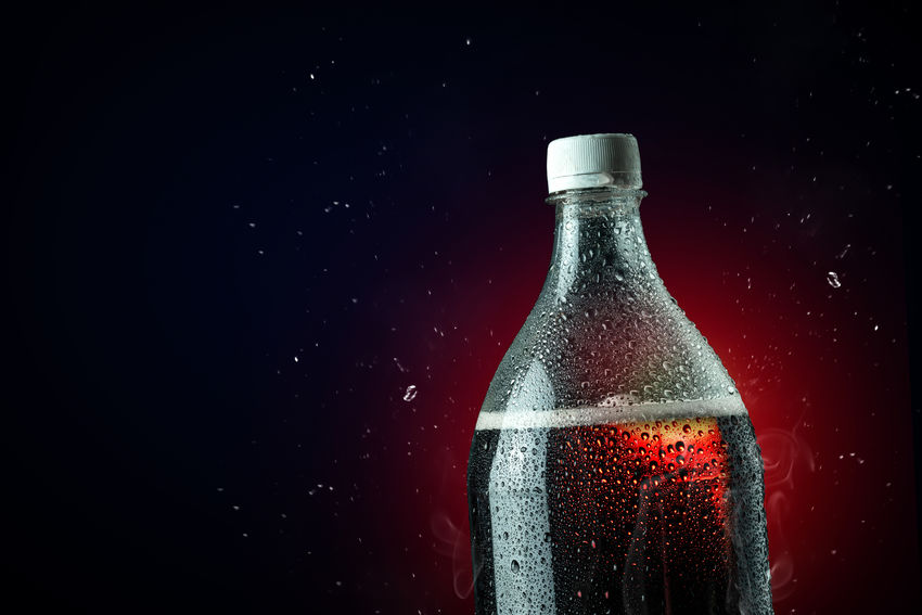 Cola bottle with ice splash on dark background. Soft drink bottle in celebration party concept. Bottle Container Refreshment Drink Food And Drink Glass - Material Indoors  No People Studio Shot Alcohol Close-up Focus On Foreground Black Background Freshness Still Life Water Impact Copy Space Water Bottle  Glass Blob Softdrink Cola Cocktail Cocacola