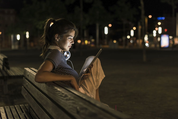Side view of a girl sitting on seat in city at night