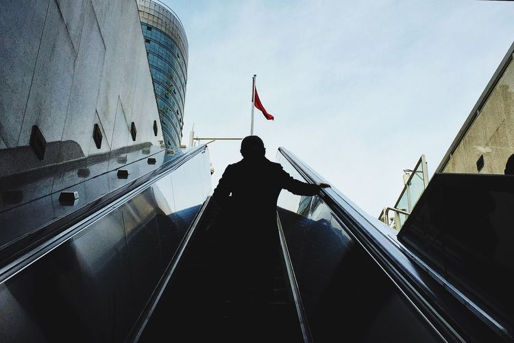 Low Angle View Of Person On Escalator Against Sky