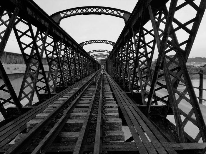 A man sitting in solitude in unused old railroad tracks in bridge against sky.