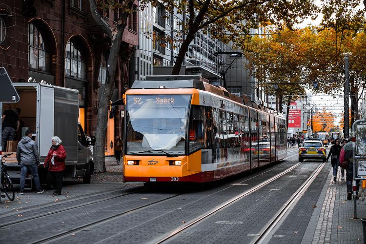 People walking on railroad tracks in city