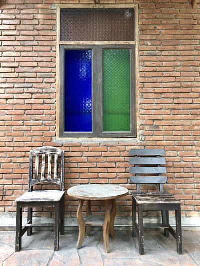 Empty chairs and table against brick wall