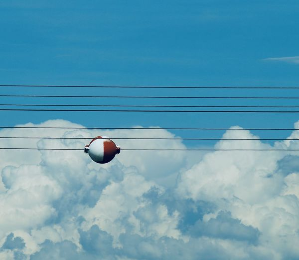 Low angle view of electrical cable against sky